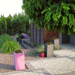 Kolorowe donice ozdobne w ogrodzie frontowym wypełnione wrzosami