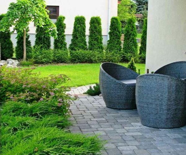 Meble ogrodowe na tarasie wypoczynkowym i rosnące obok rośliny jałowca